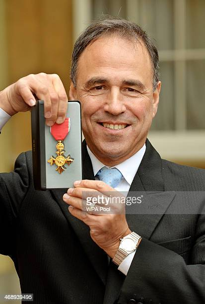 Author and screenwriter Anthony Horowitz holds his Officer of the Order of the British Empire medal after being presented to him by the Prince of...