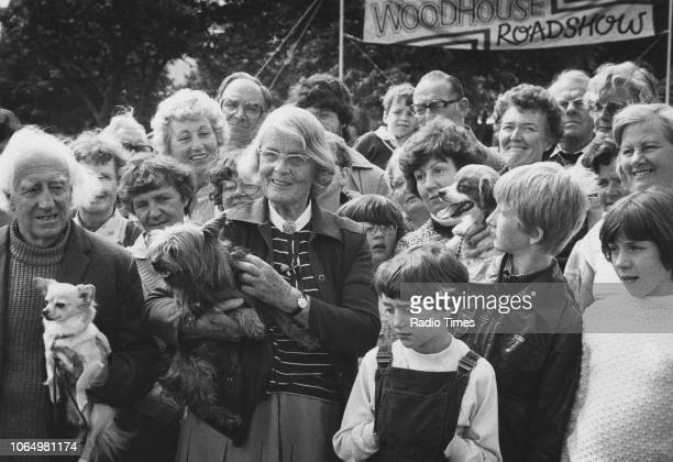 Author and television personality Barbara Woodhouse pictured holding a dog whilst talking a crowd of people during the filming of the television show...