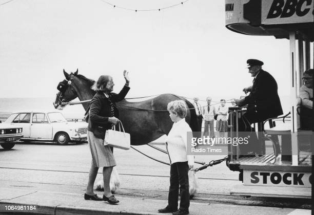 Author and television personality Barbara Woodhouse waving as she greets the driver of a horsedrawn tram during the filming of the television show...