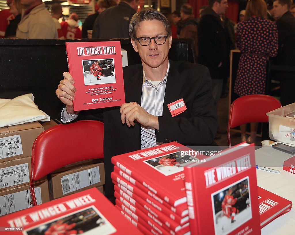 Author and TSN reporter Rob Simpson signs copies of his new book 'The Winged Wheel' in the concourse of Joe Louis Arena before a NHL game between the Vancouver Canucks and the Detroit Red Wings on February 24, 2013 in Detroit, Michigan.
