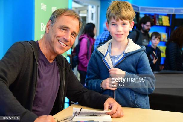 Author Anthony Horowitz poses for a photograph with a young fan at a book signing on the opening day of the Edinburgh International Book Festival on...