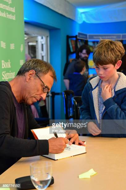 Author Anthony Horowitz signs a book for a young fan on the opening day of the Edinburgh International Book Festival on August 12 2017 in Edinburgh...