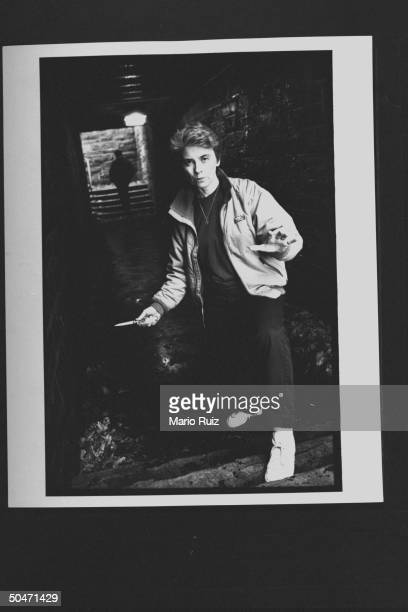 Author Camille Paglia brandishing a switch-blade knife as she poses in underground passageway.
