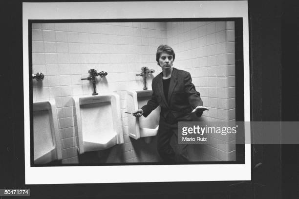 Author Camille Paglia brandishing a switch-blade knife as she poses next to urinals in a men's room.