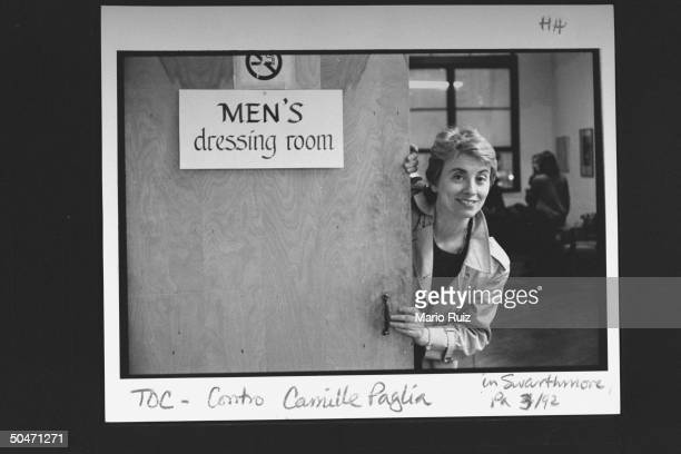 Author Camille Paglia posing next to MEN'S DRESSING ROOM sign; Swarthmore.