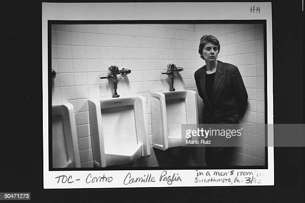 Author Camille Paglia posing next to urinals in men's room.