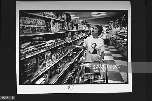Author Camille Paglia pushing cart as she peruses the shelves at a supermarket while grocery shopping.