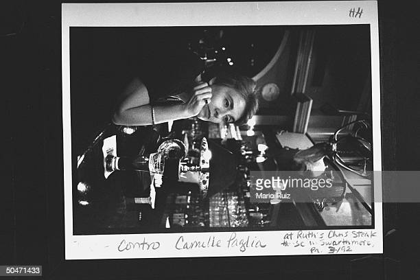 Author Camille Paglia sitting pensively over a glass of beer at the bar of her favorite watering hole, Ruth's Chris Steakhouse.