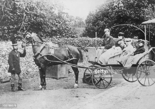 Author Charles Dickens pictured with his wife Catherine Dickens and two of their daughters seated in a horsedrawn carriage circa 1850 A man wearing a...