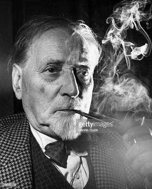 Author Compton Mackenzie wreathed in smoke from his pipe. He is the author of over 100 books including 'Sinister Street', 'Carnival' and 'Whisky...