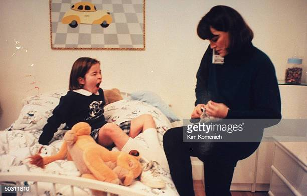Author Dr Nancy Snyderman chatting on telephone while untying daughter Kate's shoe in bedroom at home