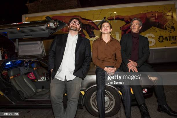 Author Ernest Cline and actors Tye Sheridan and Ben Mendelsohn sit on the hood of a Delorean in front of the Paramount Theatre at the world premiere...