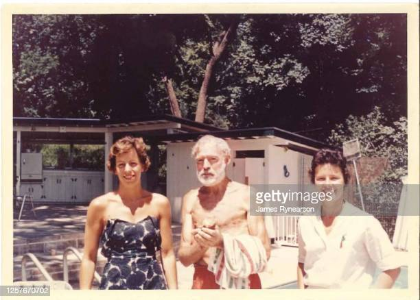 Author Ernest Hemingway poses for a photo with Anne Rynearson Cummins and Marjie Rynearson at the Rynearson family home in June 1961 in Rochester,...