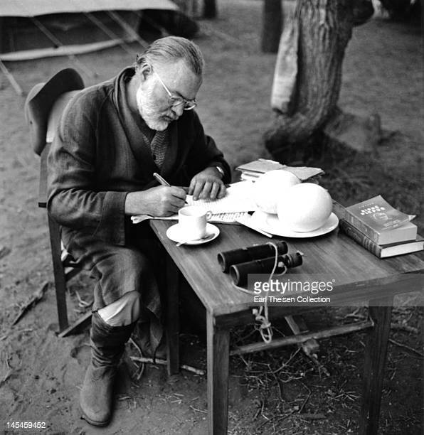 Author Ernest Hemingway writes at a portable table while on a big game hunt in September 1952 in Kenya.