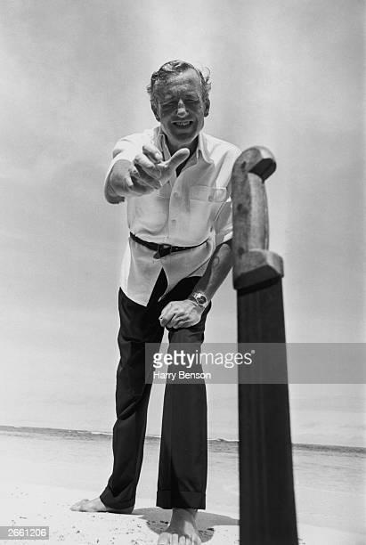 Author Ian Fleming throwing a machete knife on the beach near his home Goldeneye in Jamaica 23rd February 1964