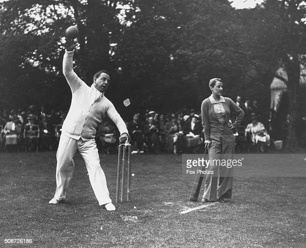 Author J B Priestley bowling as actress Beatrice Lillie waits to bat in a cricket match between the 'authors' and the 'actresses' at a gala garden...