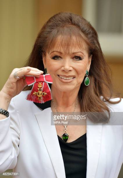 Author Jackie Collins holds her Officer of the Order of the British Empire medal after it was presented to her by Queen Elizabeth II during the...