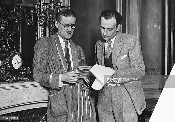 Author James Joyce looks at a set of papers with another man