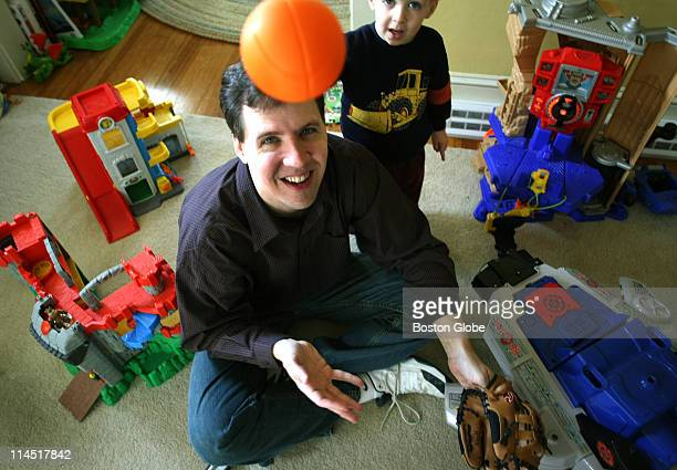 Author Jeff Kinney surrounded by his son's toys tosses a ball while his son Grant watches