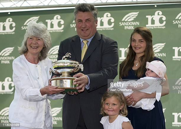 Author Jilly Cooper presents trainer Paul Nicholls and his family with his trophy for being champion traniner 2010/11 at Sandown racecourse on April...