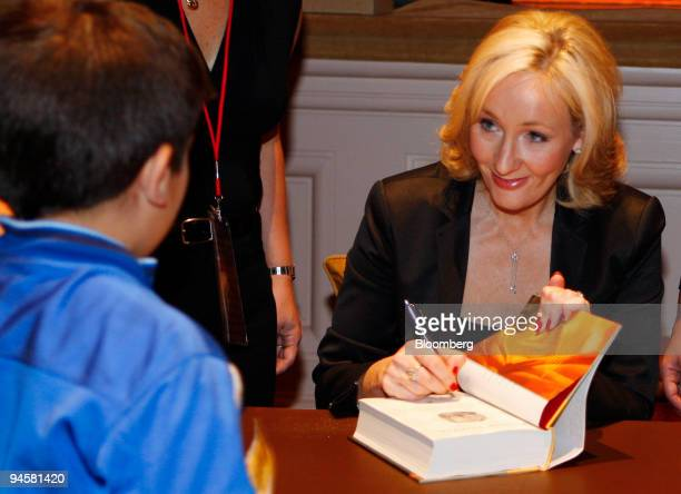 Author JK Rowling signs her book Harry Potter and the Deathly Hallows for schoolchildren during the Open Book Tour at Carnegie Hall in New York US on...