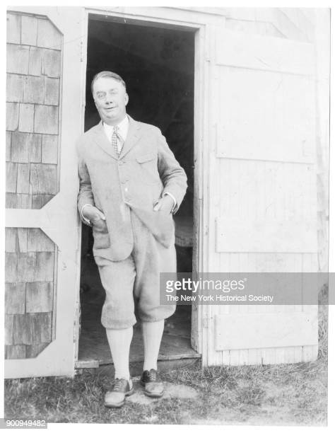 Author Joseph C Lincoln in suit jacket and breeches leaning against a barn or garage door at his home 'Crosstrees' Chatham Massachusetts 1924