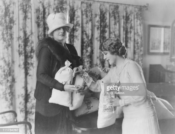 Author Kathleen Norris receives 25000 US dollars' worth of nickels and dimes from actress Mary Pickford for the 5and10 cent story 'My Best Girl'...