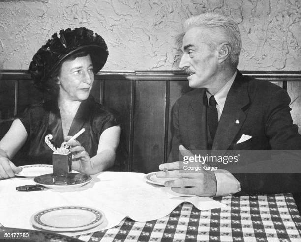 Author Lillian Hellman smoking cigarette as she chats w her lover author Dashiell Hammett while dining at Club 21