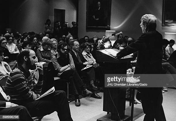 Author Northrup Frye giving a speech, wearing a dark suit and glasses, standing behind a wooden podium, both hands pressed on the podium, the...