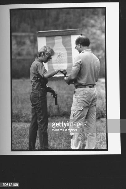 Author Patricia Cornwell taking bullets from her friend Dick Morgan as she loads her 357 Colt Python pistol while facing large bottleshaped target at...