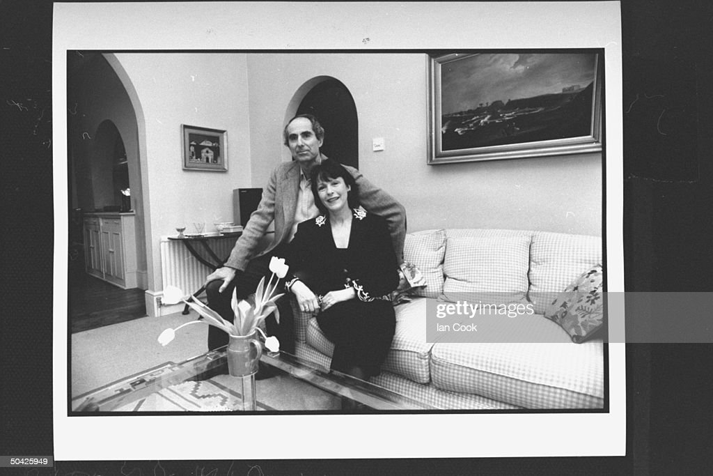 Author Philip Roth posing on couch w. his wife actress Claire Bloom in living room at home.
