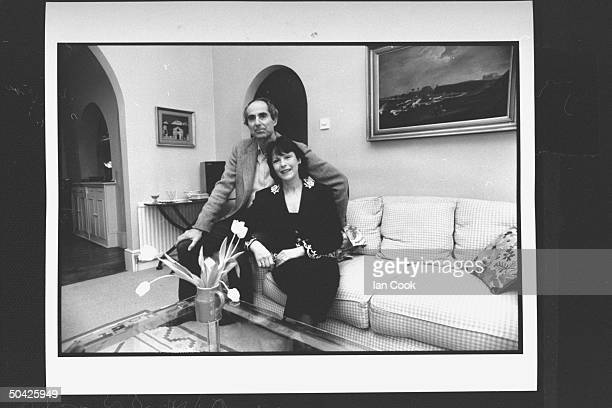 Author Philip Roth posing on couch w his wife actress Claire Bloom in living room at home