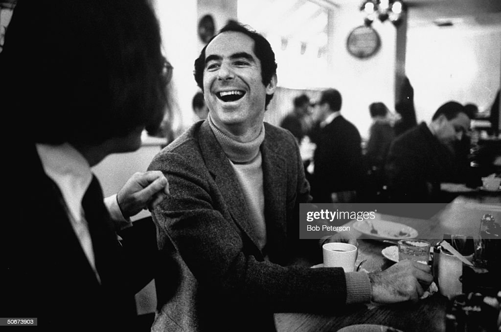 Author Philip Roth, revisiting areas where he grew up, sitting at lunch counter in Newark, New Jersey, talking to a customer.