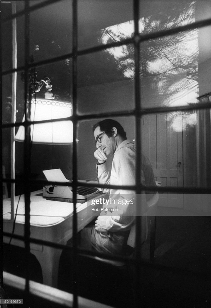 Author Philip Roth sitting at typewriter seen through panes of window, at Yaddo artist's retreat.