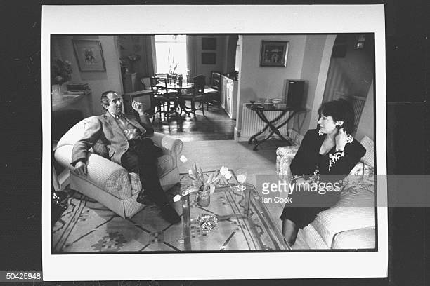 Author Philip Roth sitting in easy chair chatting w his wife actress Claire Bloom in r living room at home