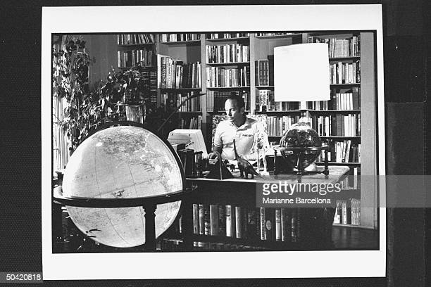 Author Rock Brynner at his desk writing on his word processor as Diplomat's map globe the largest model made looms in the foreground in his study at...
