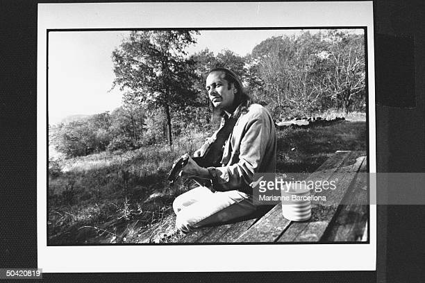 Author Rock Brynner sitting at picnic table playing his guitar at home