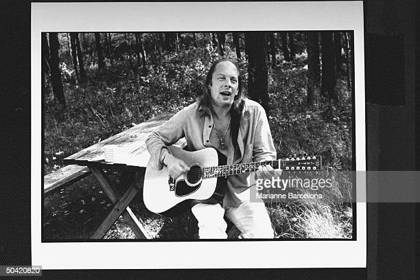 Author Rock Brynner sitting at picnic table playing his guitar singing at home