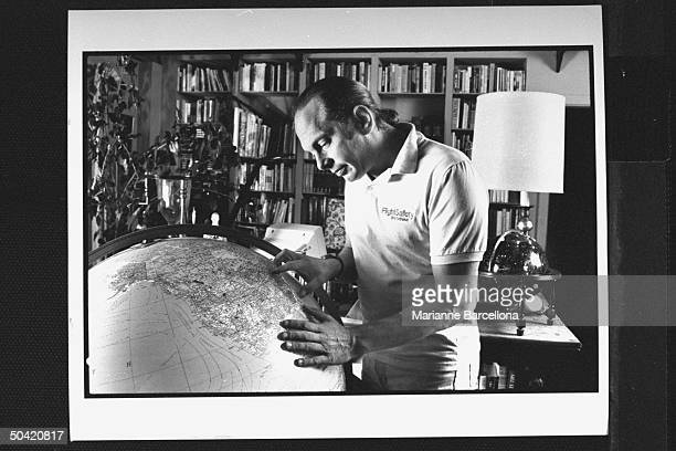 Author Rock Brynner studying his Diplomat's map globe the largest model made today at home in his study