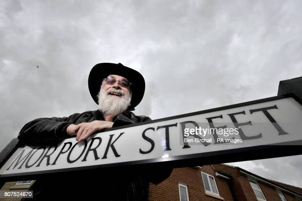 Author Sir Terry Pratchett OBE leaves leans on a roadsign during a visit to Kingwell Rise the small Somerset town which has Discworldinspired road...