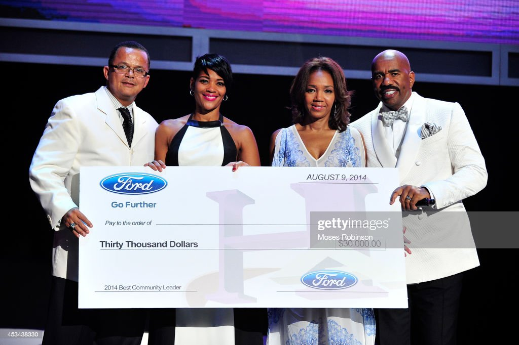 Author Stan Richards and Chereace Richards accept an award for Best Community Leader from Shawn Thompson and Steve Harvey at the 2014 Ford Neighborhood Awards Hosted By Steve Harvey at the Phillips Arena on August 9, 2014 in Atlanta, Georgia.