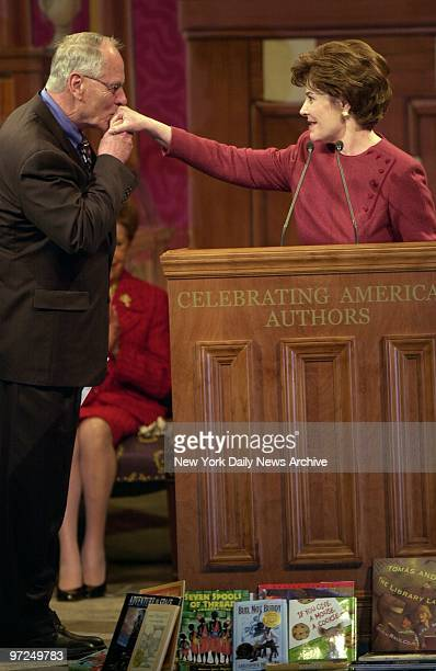 Author Stephen Ambrose kisses the hand of Laura Bush at an event celebrating America's authors in Washington