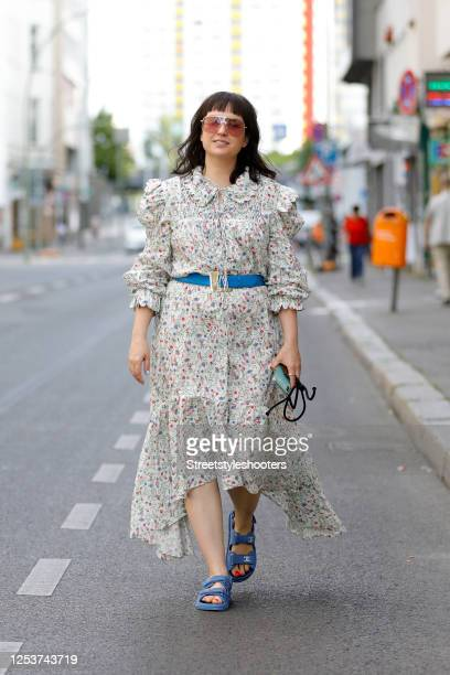 Author, TV host and influencer Vreni Frost, wearing a floral dress by Horror Vacui, a blue belt by YSL vintage, blue sandala by Chanel and sunglasses...