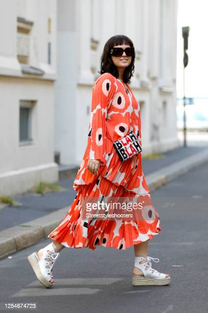 Author, TV host and influencer Vreni Frost wearing a red flower printed tunic and skirt by Marimekko, white plateau shoes by Miu Miu, a bag with the...