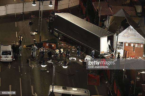 TOPSHOT Authorites continue to remove bodies hours after a truck sped into a Christmas market in Berlin on December 19 killing at least nine people...