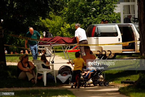 Authorities carry a body bag away from a home as neighbors look on from the sidewalk June 10 2007 in Delavan Wisconsin Six people were found fatally...