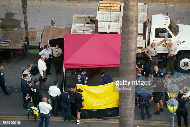 Authorities examine a corpse at the site of the deadly Santa Monica Farmer's Market crash that killed 10 people and injured 63 others George Russell...