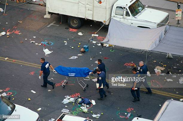 Authorities remove a corpse at the site of the deadly Santa Monica Farmer's Market crash that killed 10 people and injured 63 others. George Russell...