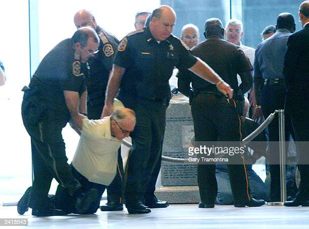 Authorities remove a Ten Commandments monument supporter who refused to leave the State Judicial Building from the monument in the rotunda during a...