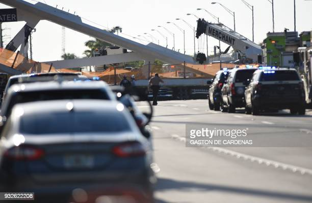 Authorities survey the scene of a pedestrian bridge collapse in Miami Florida on March 15 crushing a number of cars below and reportedly leaving...